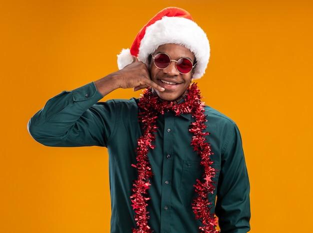 Afro-amerikaanse man in kerstmuts met slinger dragen van een zonnebril vrolijk lachend bel me gebaar staande over oranje muur