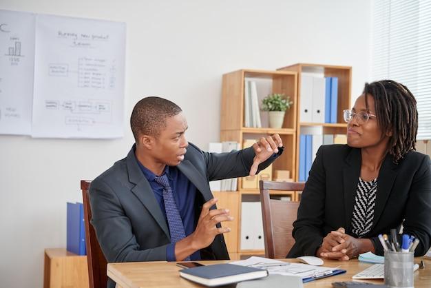 Afro-amerikaanse man in pak pitching bedrijfsidee aan vrouwelijke collega in kantoor