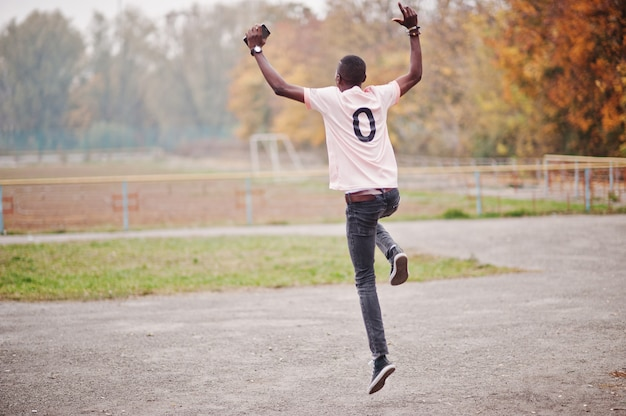 Afro-amerikaanse man in roze voetbalsport t-shirt met nul nummer.