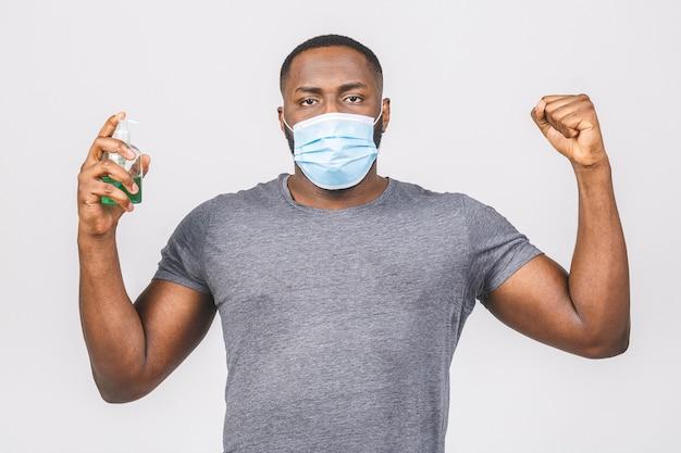 Afro-amerikaanse man in steriel gezichtsmasker. houdfles met antibacterieel ontsmettingsmiddel.