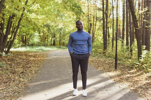 Afro-amerikaanse man in stijlvolle kleding wandelingen in zomer park