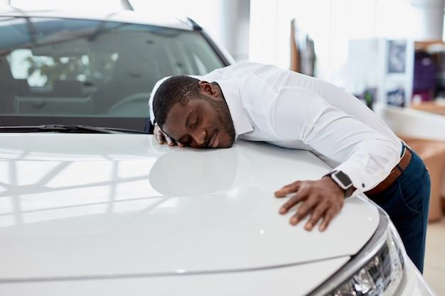 Afro-amerikaanse man knuffelt nieuwe auto waar hij over droomt