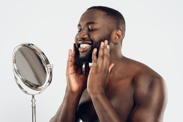 Afro-amerikaanse man maakt gebruik van vochtinbrengende lotion.