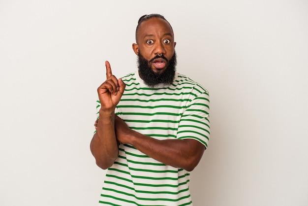 Afro-amerikaanse man met baard geïsoleerd op roze achtergrond met een geweldig idee, concept van creativiteit.