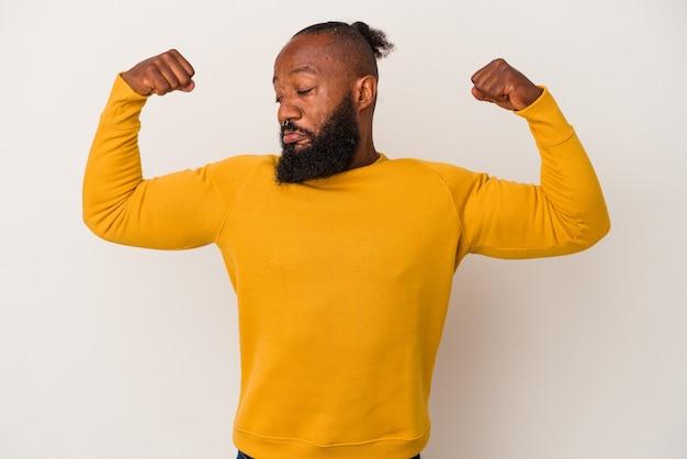 Afro-amerikaanse man met baard geïsoleerd op roze achtergrond met krachtgebaar met armen, symbool van vrouwelijke kracht