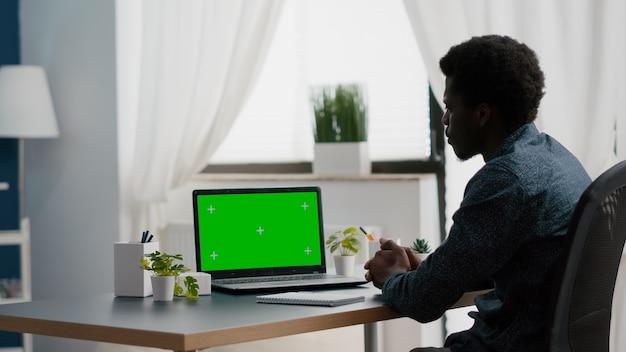 Afro-amerikaanse man met behulp van mockup laptop met groen scherm