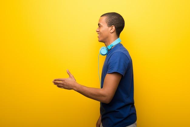 Afro-amerikaanse man met blauw t-shirt op gele achtergrond handshaking na goede deal