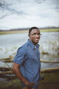 Afro-amerikaanse man met een blauw shirt en een bril die zich overdag aan een meer bevindt