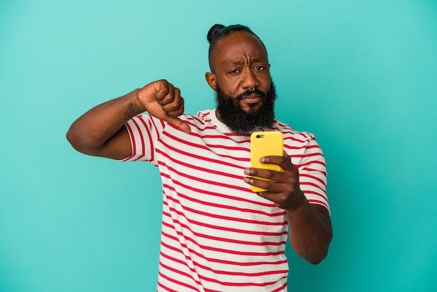 Afro-amerikaanse man met een mobiele telefoon geïsoleerd op blauwe achtergrond