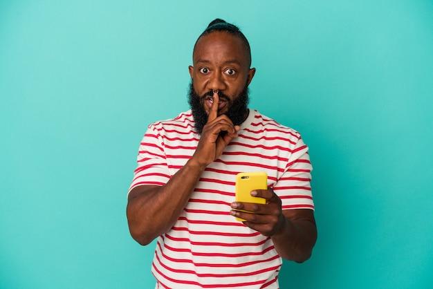 Afro-amerikaanse man met een mobiele telefoon geïsoleerd op een blauwe achtergrond die een geheim houdt