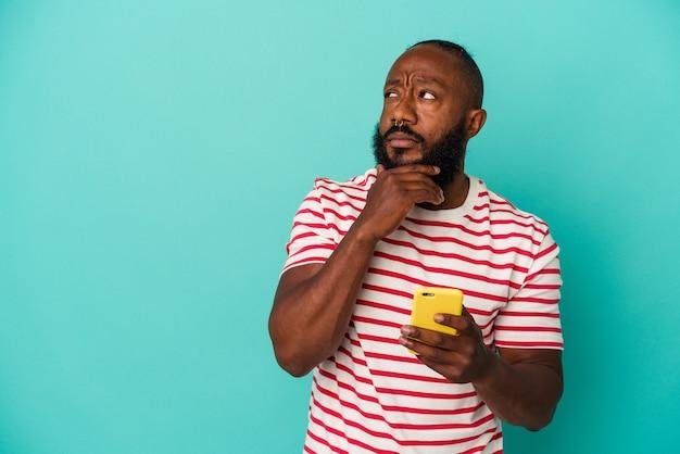 Afro-amerikaanse man met een mobiele telefoon geïsoleerd op een blauwe achtergrond zijwaarts kijkend