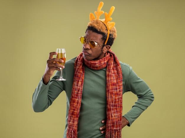 Afro-amerikaanse man met grappige rand met herten hoorns en sjaal om de nek met glas champagne kijken geïntrigeerd staande over groene achtergrond