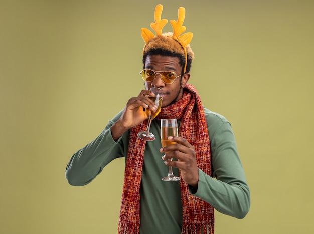 Afro-amerikaanse man met grappige rand met herten hoorns en sjaal om de nek met twee glazen champagne drinken staande op groene achtergrond