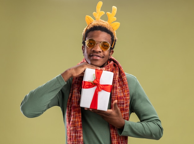 Afro-amerikaanse man met grappige rand met herten hoorns en sjaal om nek houden kerstcadeau camera kijken met glimlach op gezicht staande over groene achtergrond