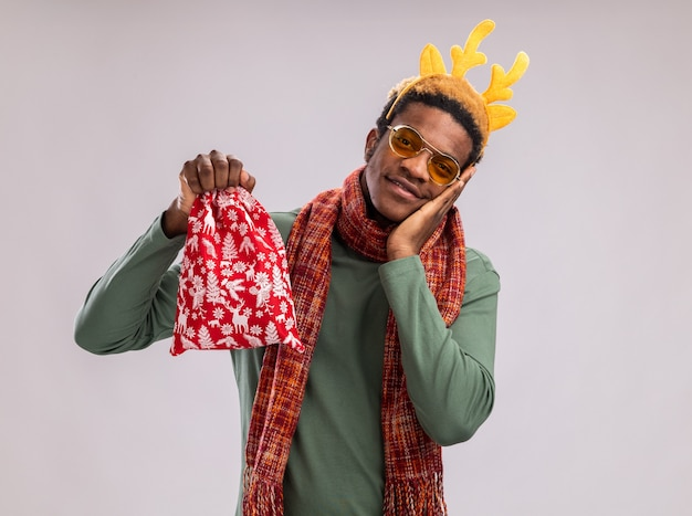 Afro-amerikaanse man met grappige rand met herten hoorns en sjaal om nek met rode kerstman tas met geschenken blij en positief glimlachend staande op witte achtergrond
