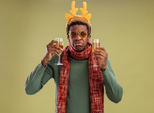 Afro-amerikaanse man met grappige rand met herten hoorns en sjaal om nek met twee glazen champagne camera kijken met droevige uitdrukking tuitte lippen staande over groene achtergrond