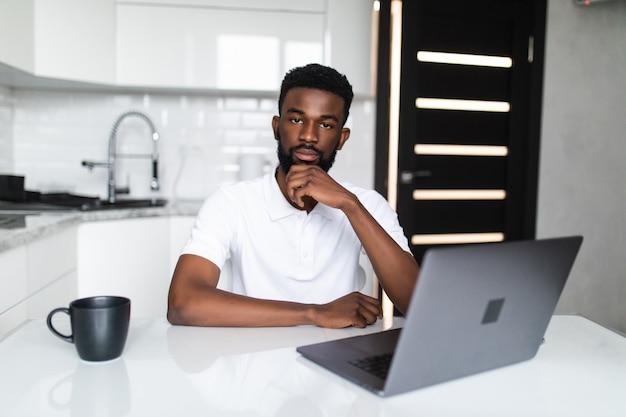 Afro-amerikaanse man met laptop in de keuken