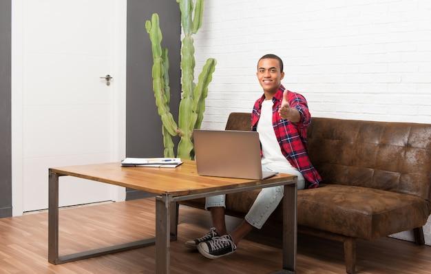Afro-amerikaanse man met laptop in de woonkamer handen schudden voor het sluiten van een goede deal