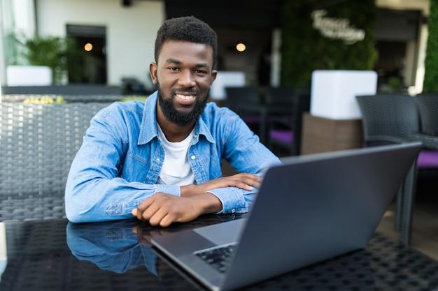 Afro-amerikaanse man met laptop in een café