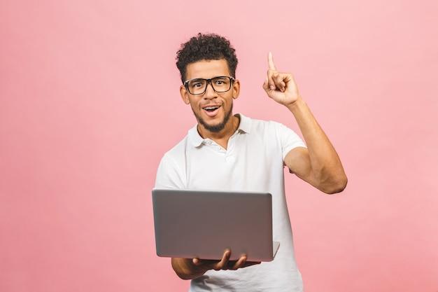 Afro-amerikaanse man met laptop verrast met een idee of vraag wijzende vinger met blij gezicht