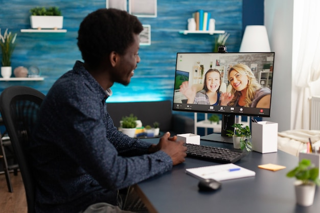 Afro-amerikaanse man met online videocall-conferentievergadering over marketingideeën met vrienden op afstand tijdens coronavirusvergrendeling. telewerkgesprek via videoconferentie op computerscherm