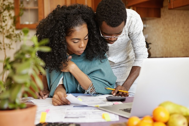 Afro-amerikaanse man met potlood berekeningen maken op de rekenmachine, zijn vrouw helpen met papierwerk