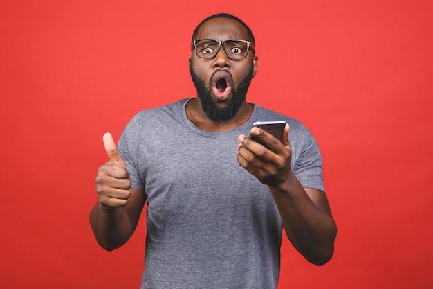 Afro-amerikaanse man met smartphone blij met grote glimlach doet ok teken, duim omhoog met vingers