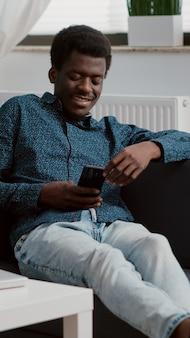 Afro-amerikaanse man met telefoon in handen die naar inhoud van online streamingdiensten kijkt