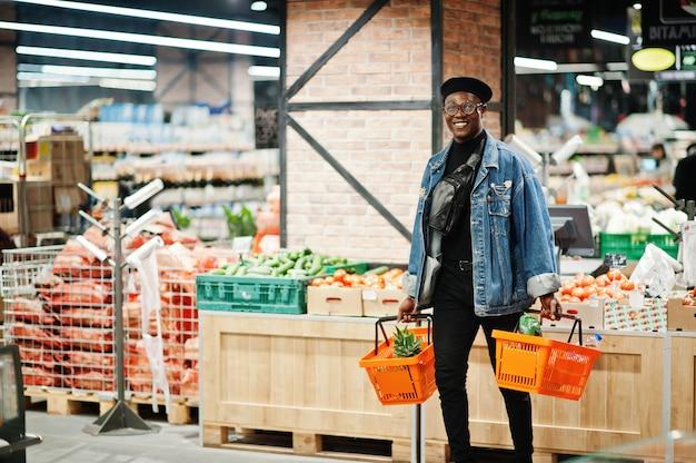 Afro-amerikaanse man met twee manden, wandelen en winkelen bij de supermarkt.