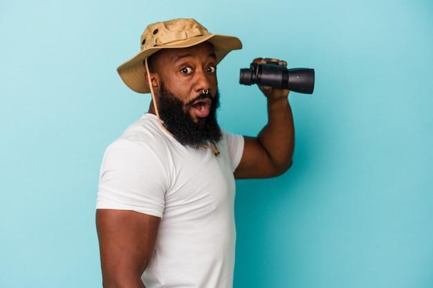 Afro-amerikaanse man met verrekijker geïsoleerd op blauwe achtergrond