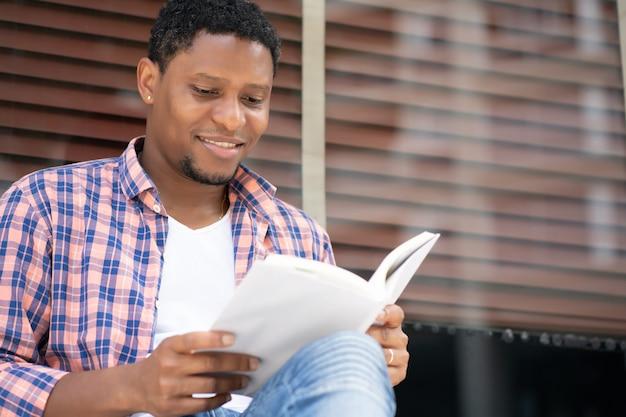Afro-amerikaanse man ontspannen en lezen van een boek zittend bij een etalage op straat.