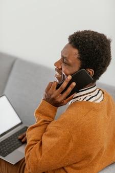 Afro-amerikaanse man op afstand werken vanuit zijn huis