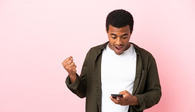 Afro-amerikaanse man op copyspace roze achtergrond verrast en stuurt een bericht