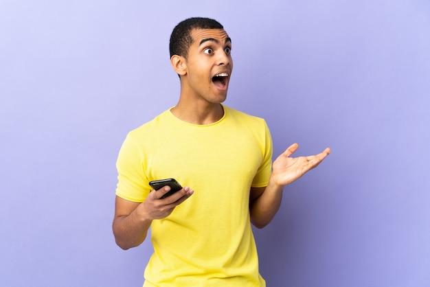 Afro-amerikaanse man op geïsoleerde paars met behulp van mobiele telefoon met verrassingsgelaatsuitdrukking