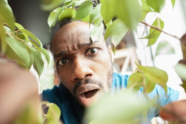 Afro-amerikaanse man op zoek naar iets op ongewone plaatsen bij hem thuis