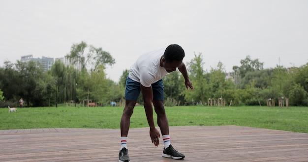 Afro-amerikaanse man opwarmen met oefeningen voor intensieve training buitenshuis. opwarming van de spieren voor het joggen. buitensport.