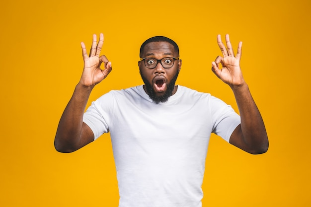 Afro-amerikaanse man over geïsoleerde muur die positief doend ok teken met hand en vingers glimlachen. succesvolle expressie.