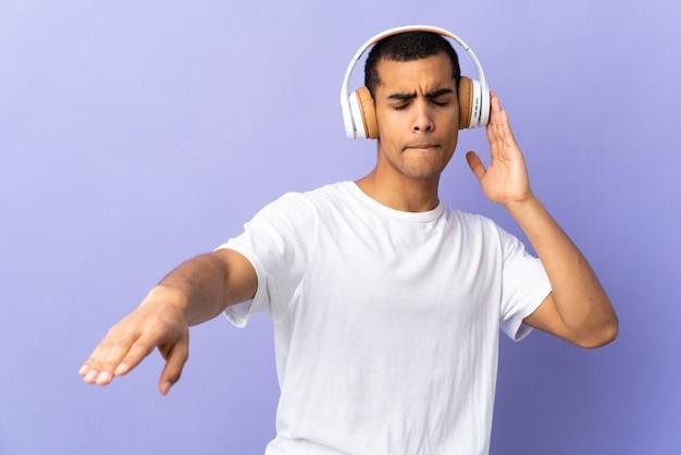 Afro-amerikaanse man over geïsoleerde paarse achtergrond muziek luisteren en dansen