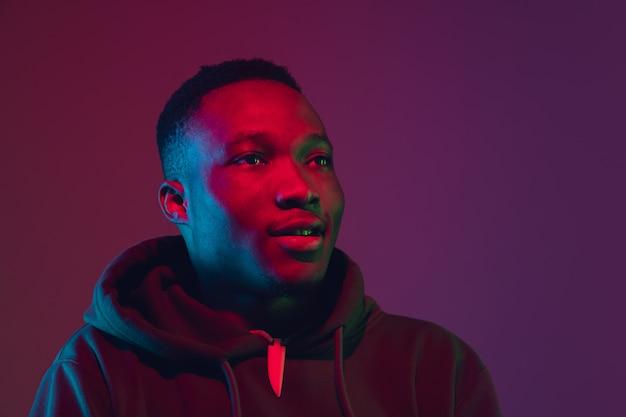 Afro-amerikaanse man portret geïsoleerd op verloop muur in neonlicht