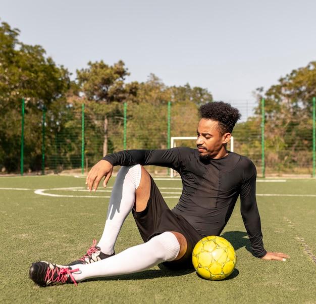 Afro-amerikaanse man poseren met een voetbal buitenshuis