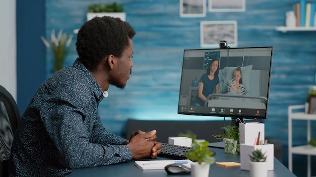 Afro-amerikaanse man praat met zijn familie die op de ziekenhuisafdeling ligt, met behulp van intenet web online teleconferentie video-oproep om contact te maken met dierbaren. webcam-app consult op afstand in de gezondheidszorg
