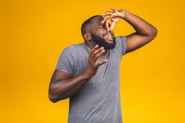 Afro-amerikaanse man ruikt iets stinkt en walgelijk, onduldbare geur, adem in met vingers op neus. slechte geuren concept.