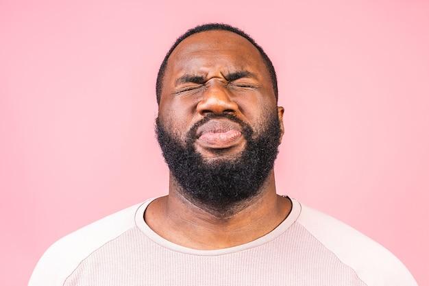 Afro-amerikaanse man ruikt naar iets stinkends en walgelijks,