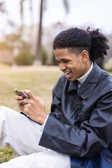 Afro-amerikaanse man spelen van videogames op zijn mobiele telefoon
