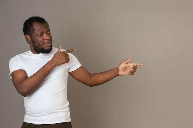Afro-amerikaanse man wijst met zijn vingers naar links, staande voor de grijze muur.