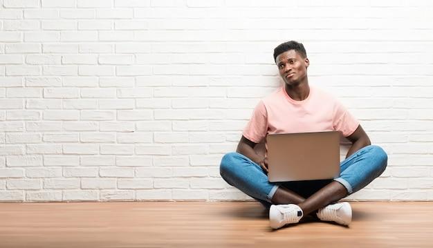 Afro-amerikaanse man zittend op de vloer met zijn laptop twijfels en met confuse gezicht expressie