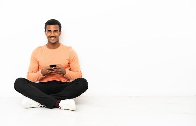 Afro-amerikaanse man zittend op de vloer over geïsoleerde copyspace-achtergrond die een bericht verzendt met de mobiel
