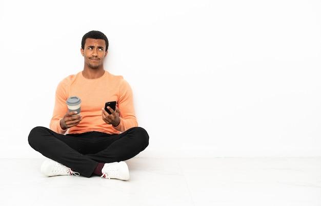 Afro-amerikaanse man zittend op de vloer over geïsoleerde copyspace-achtergrond met koffie om mee te nemen en een mobiel terwijl hij iets denkt
