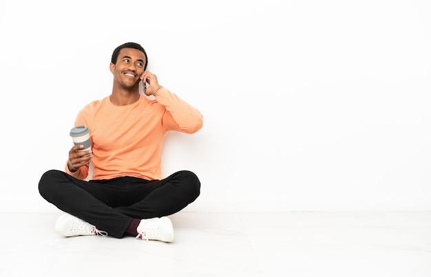 Afro-amerikaanse man zittend op de vloer over geïsoleerde copyspace-achtergrond met koffie om mee te nemen en een mobiel