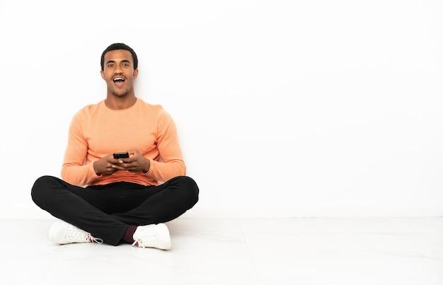 Afro-amerikaanse man zittend op de vloer over geïsoleerde copyspace-achtergrond verrast en een bericht verzendend